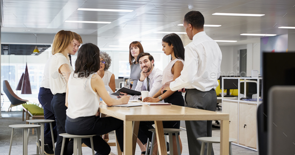 Business group brainstorming in open plan office, close up - Stock Photo - Images