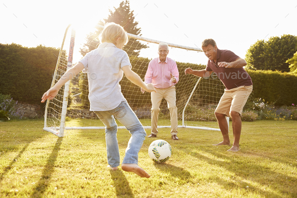Three male generations of a family playing football - Stock Photo - Images