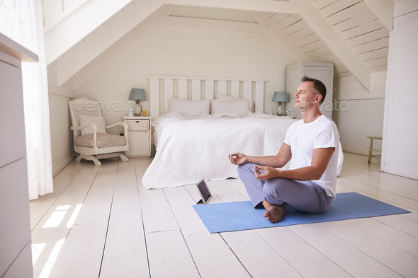 Mature Man With Digital Tablet Using Meditation App In Bedroom - Stock Photo - Images