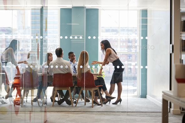 Female boss stands leaning on table at business meeting - Stock Photo - Images