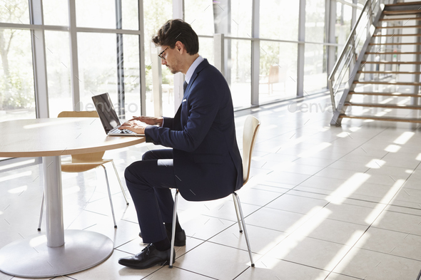 Young professional man using laptop, full length - Stock Photo - Images