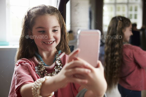 Girl Playing Dressing Up Game Taking Selfie On Mobile Phone - Stock Photo - Images