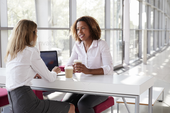 Two young businesswomen at a meeting  talking, close up - Stock Photo - Images