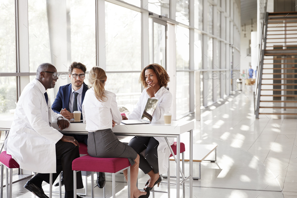 Four doctors talking at a table in a modern hospital lobby - Stock Photo - Images