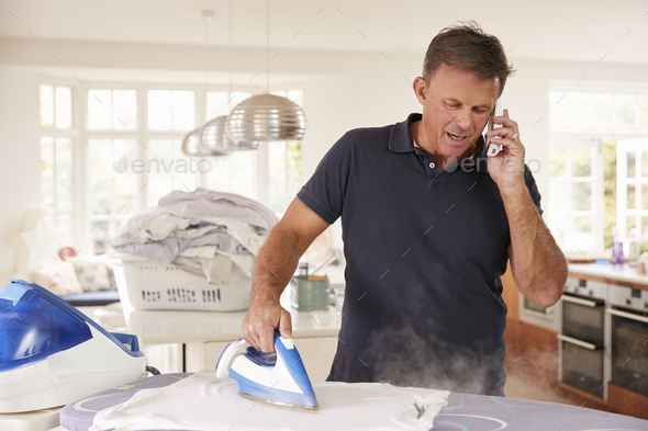 Middle aged man distracted by phone while ironing - Stock Photo - Images