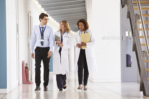 Three young male and female doctors walking in hospital - Stock Photo - Images