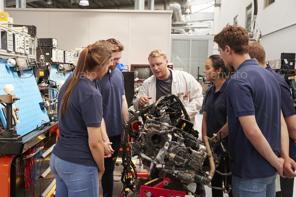 Car mechanic showing engines to apprentices - Stock Photo - Images