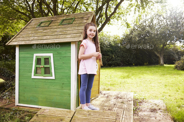 Portrait Of Girl Standing In Garden Next To Playhouse - Stock Photo - Images