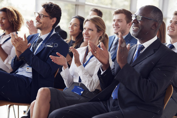 Smiling audience applauding at a business seminar - Stock Photo - Images