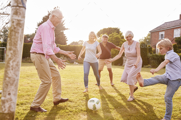 Multi generation family playing football in the garden - Stock Photo - Images