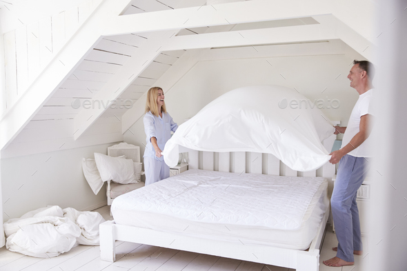 Couple Wearing Pajamas Making Bed In Morning - Stock Photo - Images