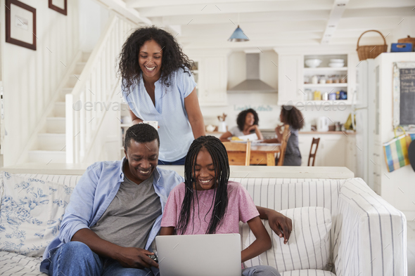 Family With Teenage Daughters Sitting On Sofa With Laptop - Stock Photo - Images