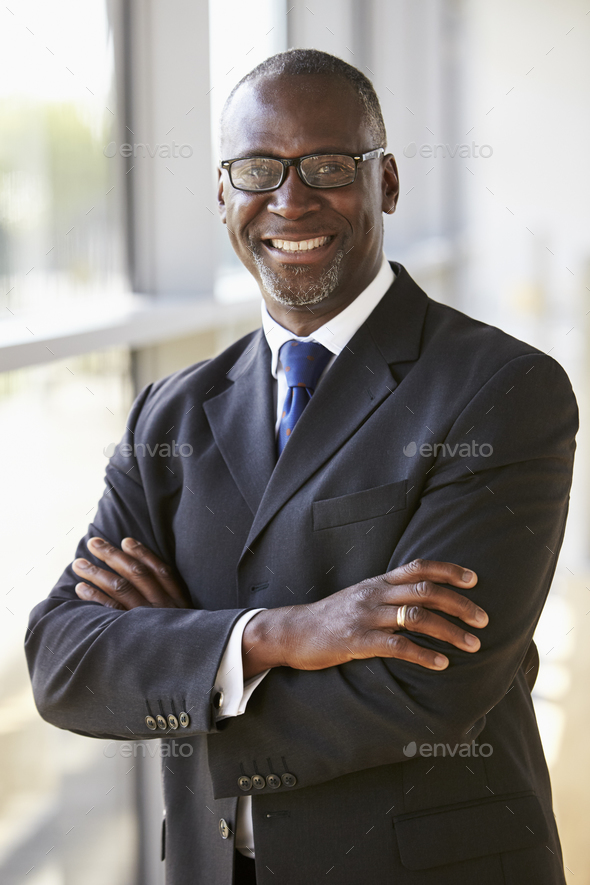 Portrait of a smiling businessman with arms crossed - Stock Photo - Images