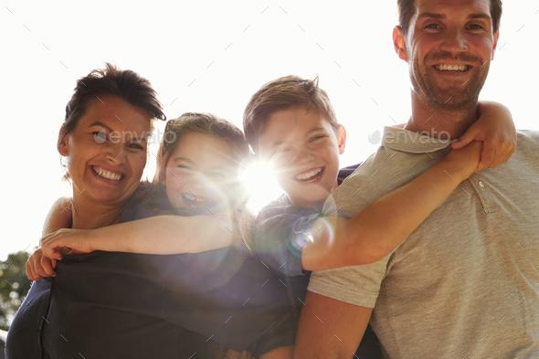 Portrait Of Parents Giving Children Piggyback In Garden - Stock Photo - Images