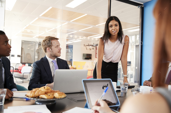 Female boss addressing team in a meeting, over shoulder view - Stock Photo - Images