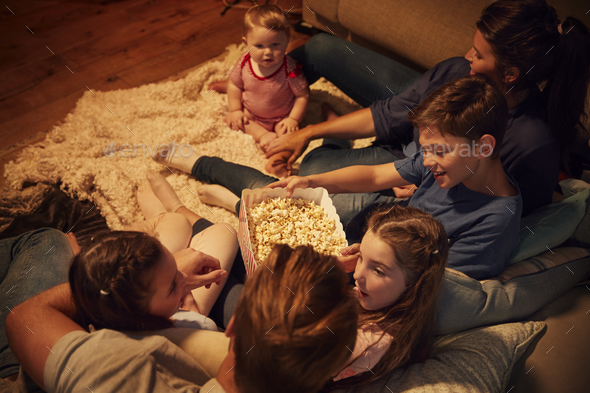 Overhead View Of Family Enjoying Movie Night At Home Together Stock Photo by monkeybusiness