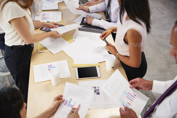 Business group brainstorming at a table, mid section - Stock Photo - Images
