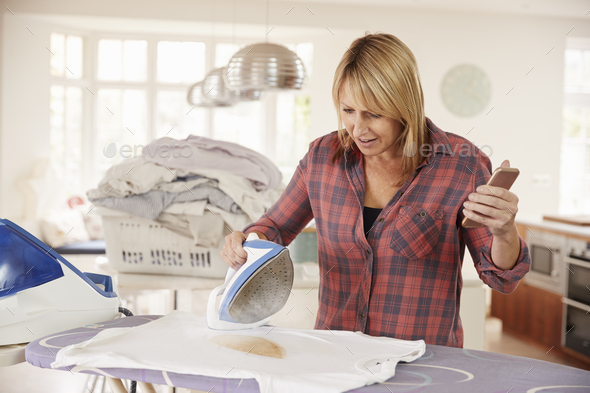 Distracted middle aged woman burns t shirt while ironing - Stock Photo - Images
