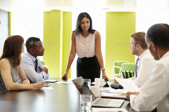 Female boss stands addressing team at informal work meeting - Stock Photo - Images