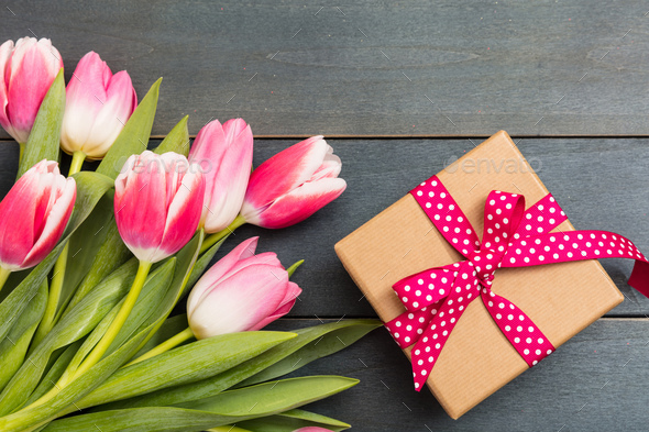 Women's day. Pink tulips and a gift on blue background, top view - Stock Photo - Images