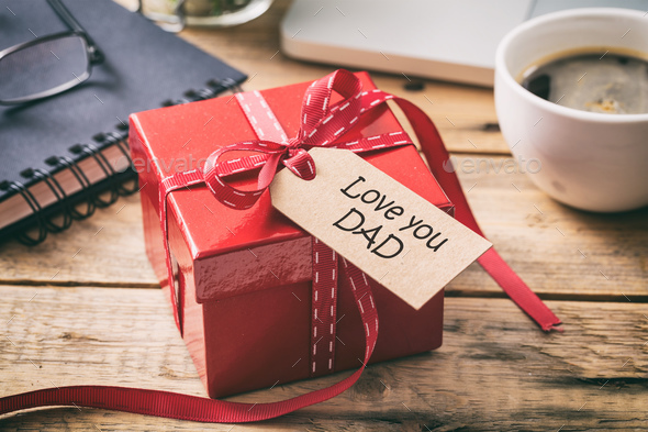 Father's day. Red gift box with love you dad tag, blur office desk background - Stock Photo - Images