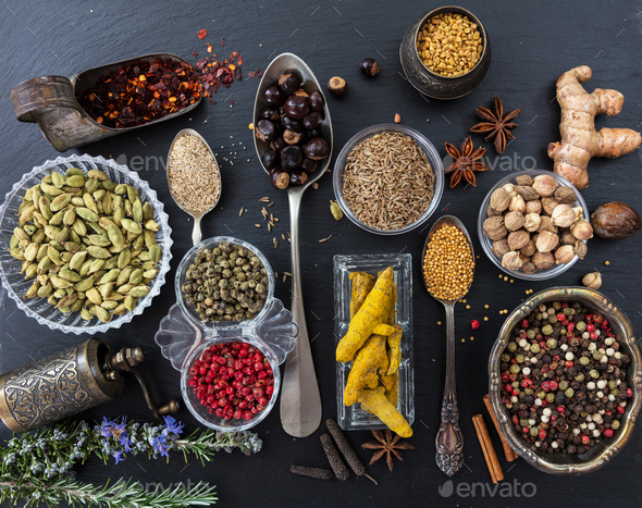 Variety of colorful spices and herbs on black stone background, top view - Stock Photo - Images