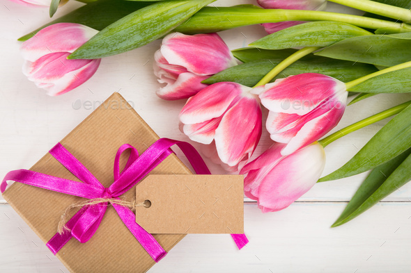 Mothers day. Pink tulips and a blank card gift on white background, top view, copy space - Stock Photo - Images