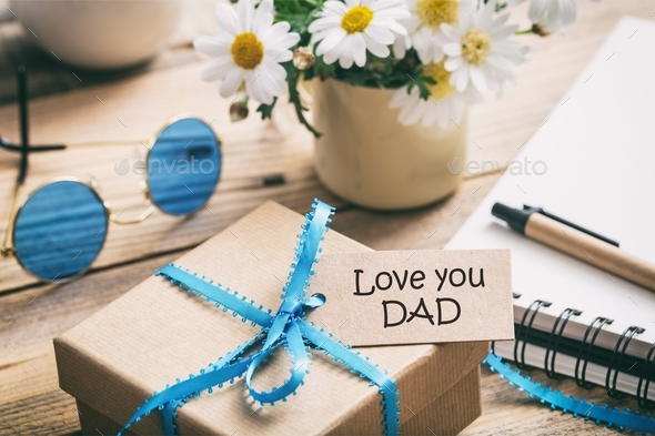 Father's day. Gift box with love you dad tag, blur office desk background - Stock Photo - Images