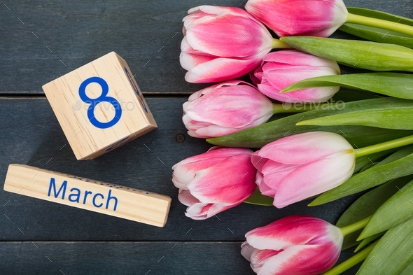 Women's day concept. Pink tulips and the March 8th date on blue background - Stock Photo - Images
