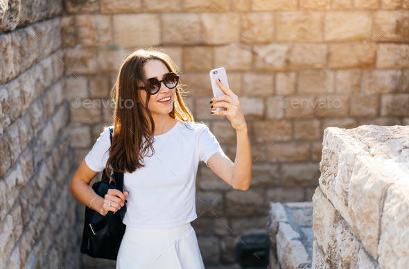 Happy young woman taking selfie - Stock Photo - Images