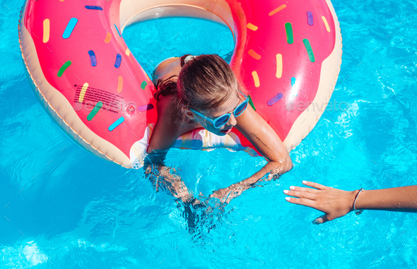 Girl on inflatable ring in swimming pool - Stock Photo - Images