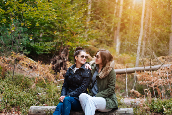 two beautiful girls sat down in the forest - Stock Photo - Images