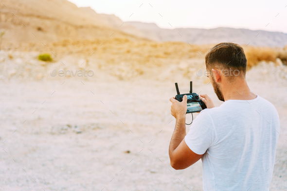 Guy controls drone with remote control - Stock Photo - Images