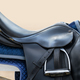 Black English saddle hanging on fence near stables. - PhotoDune Item for Sale