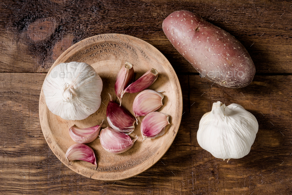 aerial take of whole garlic cloves and heads in rustic wood - Stock Photo - Images