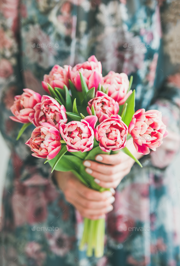 Woman in colorful dress holding bouquet of pink tulips - Stock Photo - Images