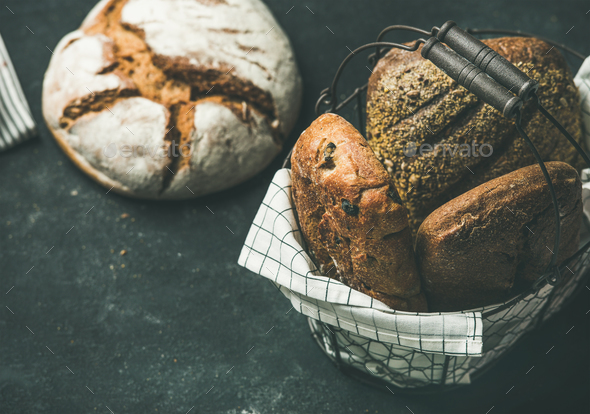 Various bread loaves over black background, copy space - Stock Photo - Images