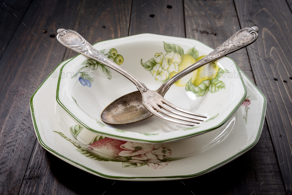 porcelain floral pattern plates with antique cutlery - Stock Photo - Images