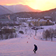 Snowboarder Going down Mountain into Incredible Sunset