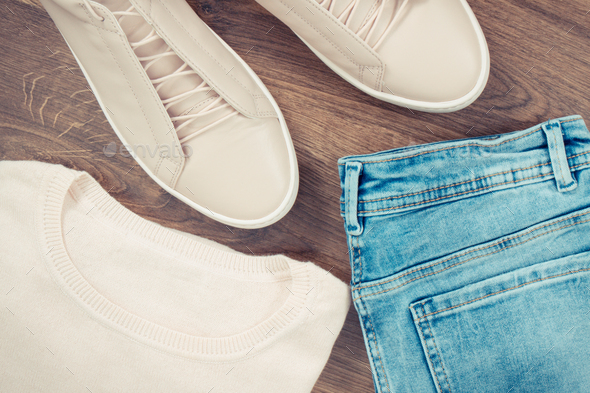Vintage photo, Womanly leather shoes, jeans pants and sweater on rustic boards - Stock Photo - Images