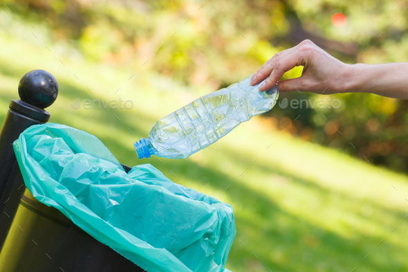 Hand of woman throwing bottle into recycling bin, littering of environmental - Stock Photo - Images