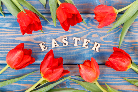 Inscription Easter and red tulips on boards as festive decoration - Stock Photo - Images