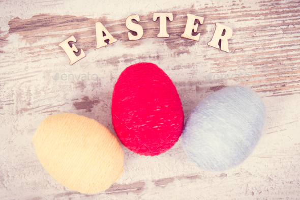 Vintage photo, Inscription Easter and eggs wrapped woolen string on rustic board, festive decoration - Stock Photo - Images