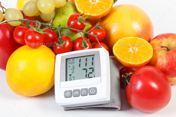 Blood pressure monitor and fresh ripe fruits with vegetables, healthy lifestyle and nutrition - Stock Photo - Images