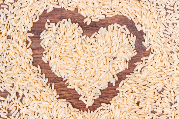 Heart shaped brown rice on rustic board - Stock Photo - Images