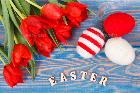 Inscription Easter, red tulips and eggs wrapped woolen string on boards, festive decoration - Stock Photo - Images