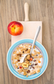 aerial shot of bowl of cereal with fresh peach on natural wooden - PhotoDune Item for Sale