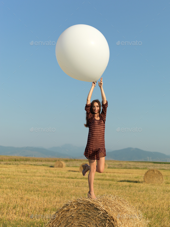 happy woman jumping white balloon hay stack - Stock Photo - Images