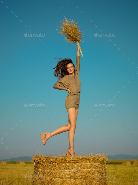joyful young woman jumping on hay stack - Stock Photo - Images