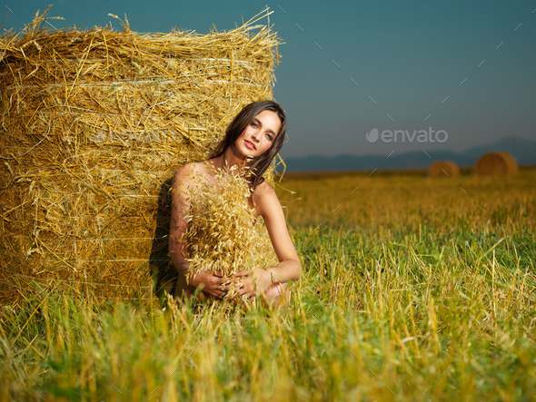 beautiful nude woman sitting near hay stack - Stock Photo - Images